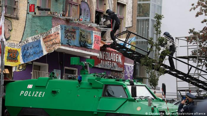 A green police truck and two policemen climb the stairs to a house with a banner and graffiti (Christophe Gateau / dpa / picture-alliance)