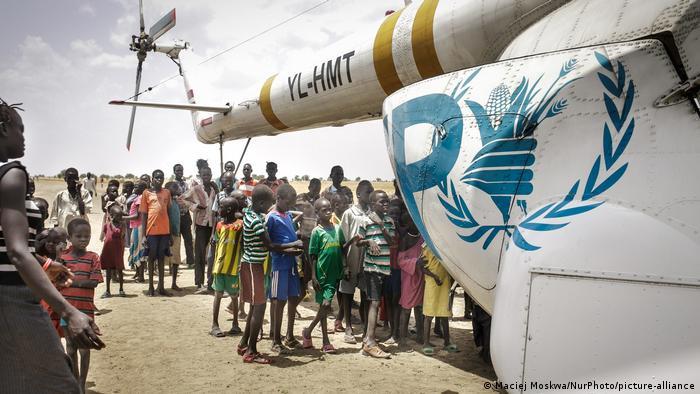 Crianças e adolescentes ao lado de um avião da ONU no Sudão do Sul