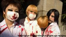 Young Japanese women wearing face masks, heavy dark eye makeup and white shirts splashed with fake blood