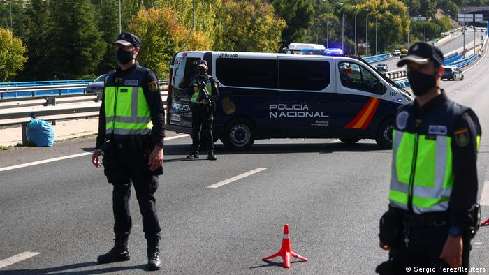 Spanish National Police officers wearing protective masks stand at a traffic checkpoint