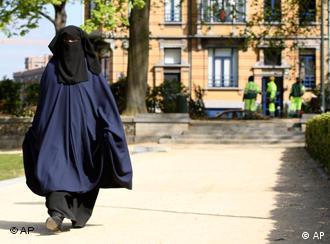 Una mujer vestida con burka camina por un parque en Bruselas.