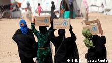 FILE PHOTO: People displaced from fightings between the Syrian Democratic Forces and Islamic State militants carry boxes of food aid given by UN's World Food Programme at a refugee camp in Ain Issa, Syria October 10, 2017. REUTERS/Erik De Castro/File Photo