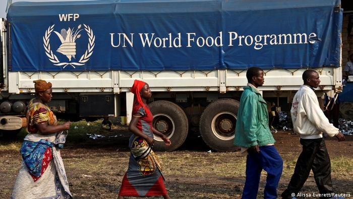 Displaced Congolese citizens walking past a World Food Programme truck (Alissa Everett/Reuters)