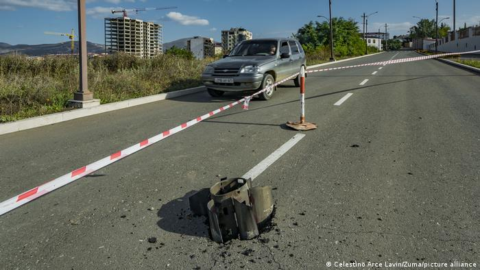 An unexploded rocket stuck in the road. It is cordoned off. A car drives past it.