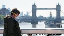 A man walks close to Tower Bridge wearing a mask (Dominic Lipinsk/empics/picture-alliance)