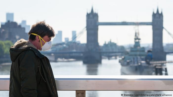 A man walks close to Tower Bridge wearing a mask