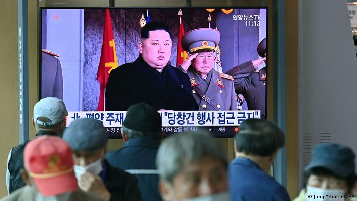 People watch a television news broadcasting a file footage of North Korea's leader Kim Jong Un