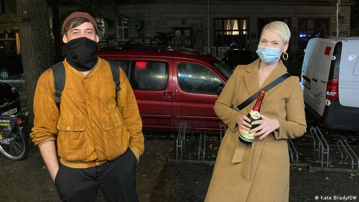 Dominik and Eilen, wearing masks and carrying a bottle of sparkling wine in Berlin