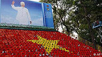 Portrait of Vietnam's revolutionary leader Ho Chi Minh looms over the national flag formed by students holding signs during a ceremony in Ho Chi Minh City