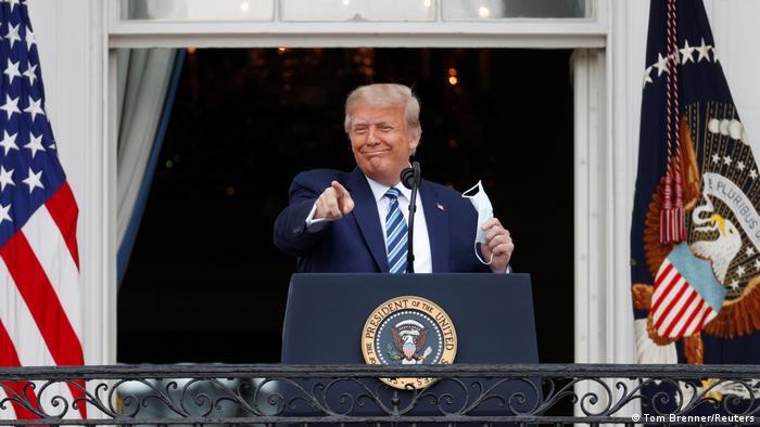 Дональд Трамп с медицинской маской в руке и флаг США на балконе Белого дома