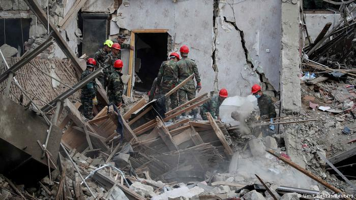 Search and rescue teams work on the blast site hit by a rocket