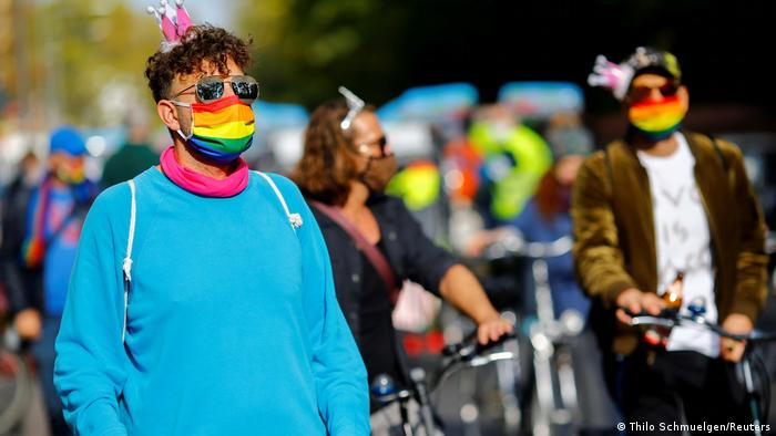 A Pride participant in a rainbow mask