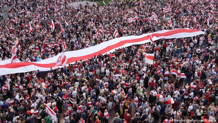 Участники протестов в Минске с бело-красно-белыми флагами