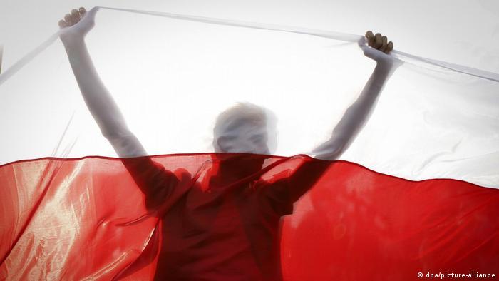 Протестующий держит бело-красно-белый флаг на акции протеста в Минске.