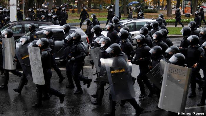 Милиционеры со щитами и в шлемах бегут по минской улице