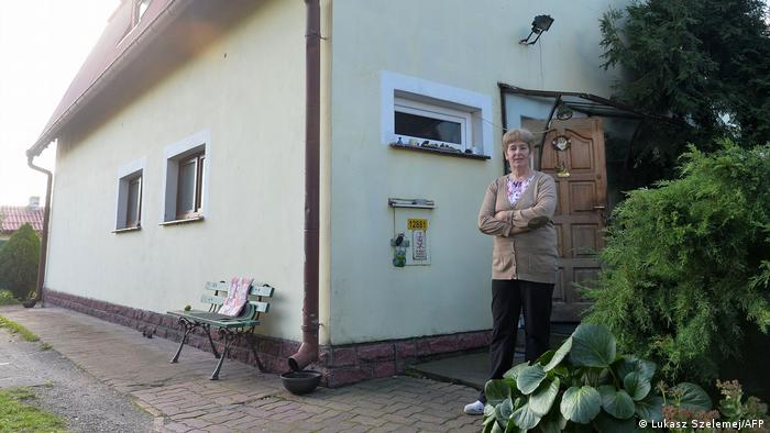 Halina Paszkowska stands outside her house