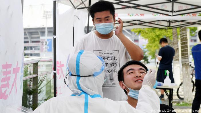 A man being tested for coronavirus outside the Qingdao Sports Center in Qingdao