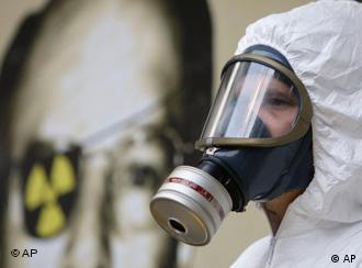 Ein Mann in einem weißen Schutzanzug mit einer Atemmaske steht vor dem schwarz-gelben Symbol für radioaktive Strahlung (Foto: AP)