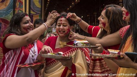 Indian women decorate each other with sindoor, vermillion powder (Tumpa Mondal/picture-alliance/Photoshot)