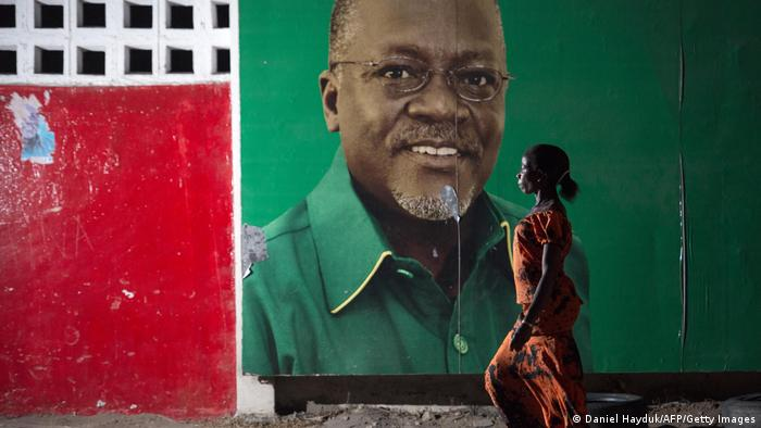 A woman walks past an election billboard after ruling party Chama Cha Mapinduzi (CCM) candidate John Magufuli