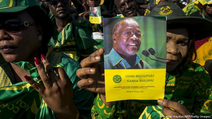A supporter holds a booklet with a photo of presidential candidate John Magufuli