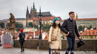 Прохожие в масках на одном из мостов в Праге