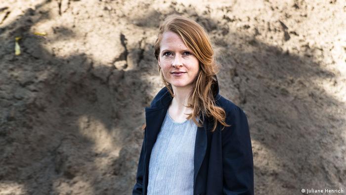 Porträtfoto Anja Kampmann mit langen rotblonden Haaren und dunkelblauen Mantel vor einem hellbraunen Erdhügel (Foto: Juliane Henrich).
