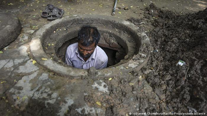 An Indian manual scavenger cleans a manhole in Jantar Mantar, India