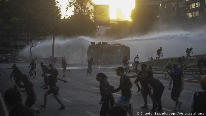 Foto de manifestantes que huyen de un camión lanza-agua en Chile