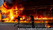 Demonstrators throw a bicycle into a burning bus station during a protest against the government's labor reforms Jakarta, Indonesia, October 8. Antara Foto/Dhemas Reviyanto/ via REUTERS