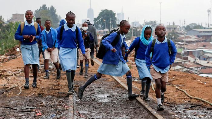 Kenyan students walking on railway