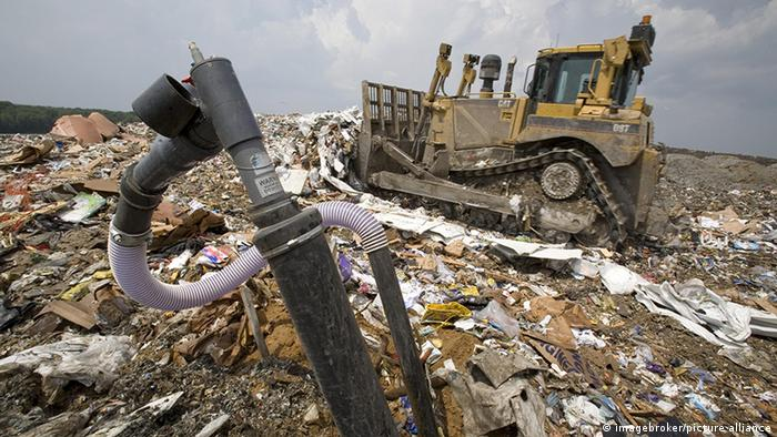 Há uma espécie de bomba sobre um lixão. Ao fundo, uma escavadeira anda sobre o lixo.