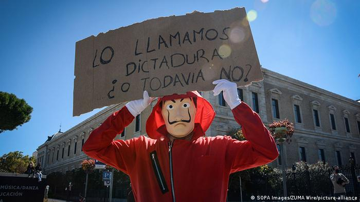 A person in a mask holding up a sign (SOPA Images/ZUMA Wire/picture-alliance)