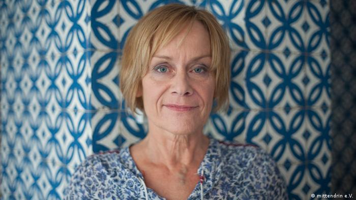 Porträt von Eva-Maria Thoms mit einem auffälligen blauen Hintergrund