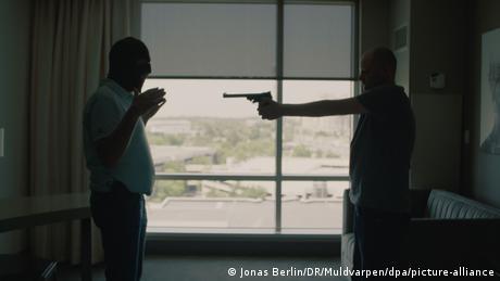 Ein Mann richtet eine Pistole auf einen anderen Mann. Dahinter ist ein Fenster zu sehen.