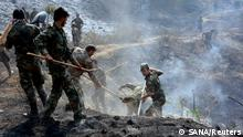 Army soldiers help firefighters to contain wildfires in Latakia province, Syria in this handout released by SANA on October 9, 2020. Picture taken October 9, 2020. SANA/Handout via REUTERS ATTENTION EDITORS - THIS IMAGE WAS PROVIDED BY A THIRD PARTY. REUTERS IS UNABLE TO INDEPENDENTLY VERIFY THIS IMAGE.