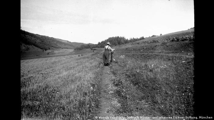 Das Foto zeigt Gabriele Münter, wie sie ihr Fahrrad über einen Feldweg schiebt. (Wassily Kandinsky, Gabriele Münter- und Johannes Eichner-Stiftung, München)