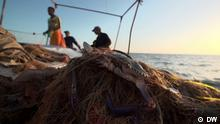 Fishermen on a boat and a crab caught in a net