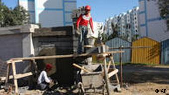Chinese workers build a wall at a housing project