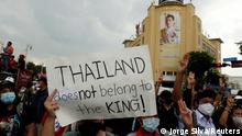 A pro-democracy demonstrator holds a placard as they walk past a portrait of King Maha Vajiralongkorn during a Thai anti-government mass protest, on the 47th anniversary of the 1973 student uprising, in Bangkok, Thailand October 14, 2020. REUTERS/Jorge Silva
