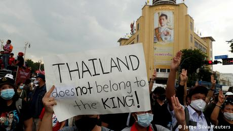 A pro-democracy demonstrator holds a placard as they walk past a portrait of King Maha Vajiralongkorn during a Thai anti-government mass protest