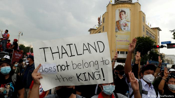 A protester holds a sign saying Thailand does not belong to the king