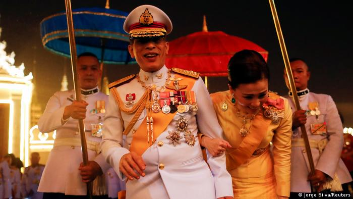 Thailand's King Maha Vajiralongkorn and Queen Suthida greet royalist supporters who gathered outside the Grand Palace