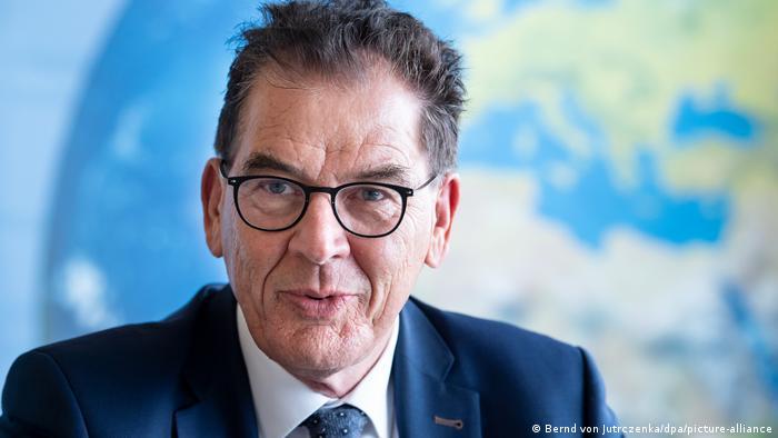 Porträt Entwicklungsminister Gerd Müller vor Weltkarte