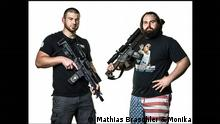 two men holding guns, one in US flag shorts, a photo from the book Divided we stand by Mathias Braschler and Monika Fischer
