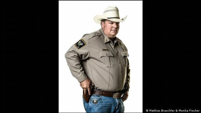 A sheriff wearing a 10 gallon white hat with hand on gun holster, a photo from the book 'Divided We Stand' by Mathias Braschler and Monika Fischer