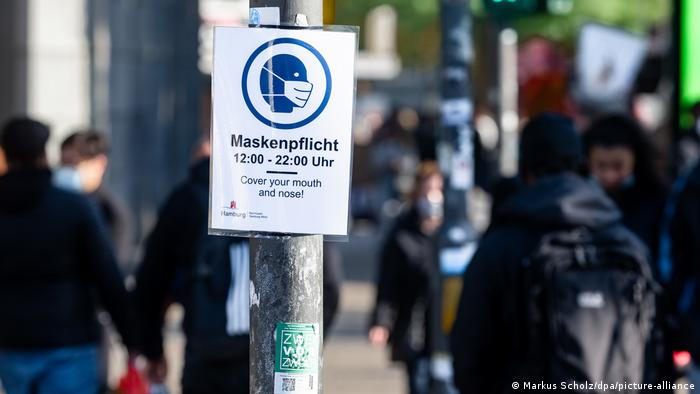 Cartaz numa rua de Hamburgo avisa aos pedestres do uso obrigatório de máscara entre 12 e 22 horas.
