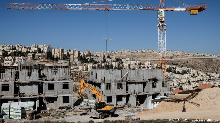 A building site in the West bank. A crane and a digger are on site next to several buildings in the process of being built. There is a city in the background.