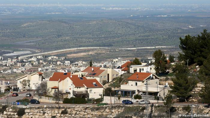 A picture taken from behind the Israeli settlement of Negahot (foreground) shows the Palestinian village of Beit Awa (C) lying before Israel's separation barrier, west of Hebron in the occupied West Bank on January 27,2020.
