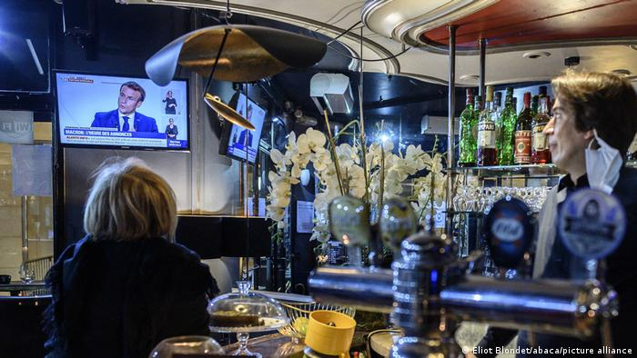 President Macron watched on television by people in a bar